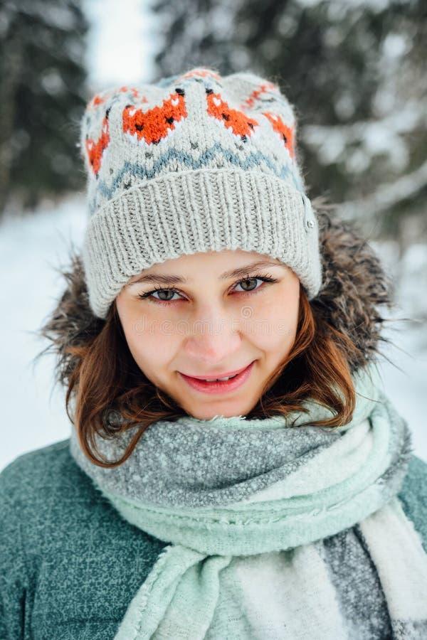 Utomhus- slut upp ståenden av den unga härliga lyckliga flickan, bärande stilfull stucken vinterhatt royaltyfri fotografi