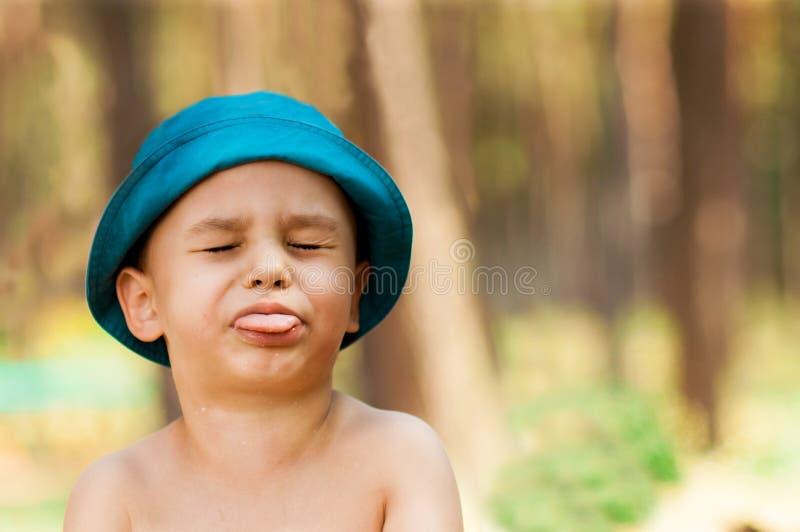 Utomhus- slut upp ståenden av pysen i en hatt Bakgrund en person, barn, 4-5 gamla år royaltyfri foto