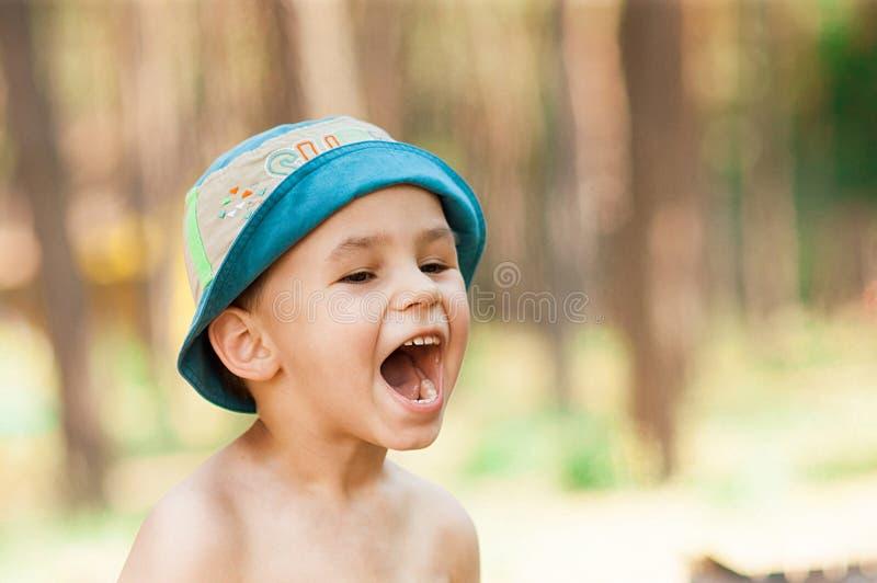 Utomhus- slut upp ståenden av pysen i en hatt Bakgrund en person, barn, 4-5 gamla år royaltyfria bilder