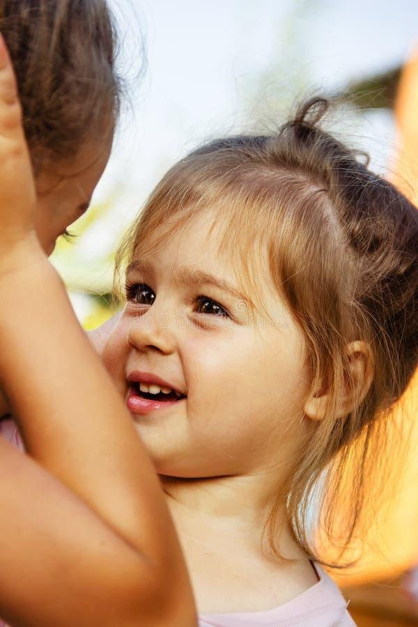 Utomhus- slut upp ståenden av två spela gulliga små flickor royaltyfri foto