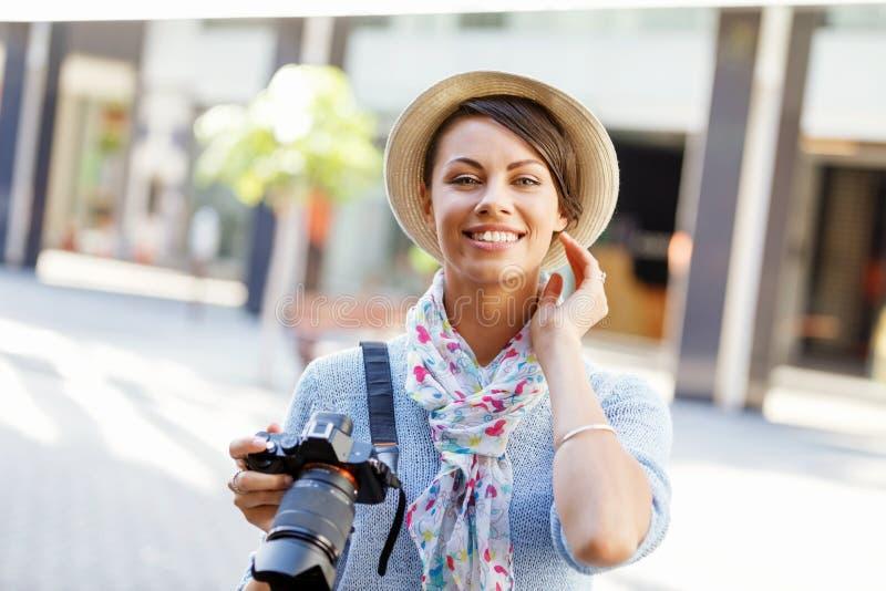 Utomhus- sommar som ler livsstilståenden av den nätta unga kvinnan med kameran fotografering för bildbyråer