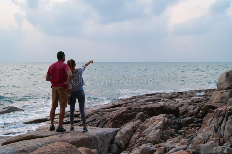 Utomhus- sommarstående av förälskat posera för unga romantiska par på den fantastiska stenstranden, arkivfoto