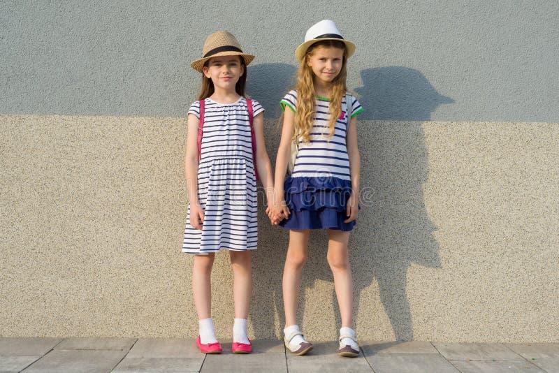 Utomhus- sommarstående av två lyckliga flickavänner 7, 8 år som rymmer händer Flickor i randiga klänningar, hattar med ryggsäcken royaltyfria bilder