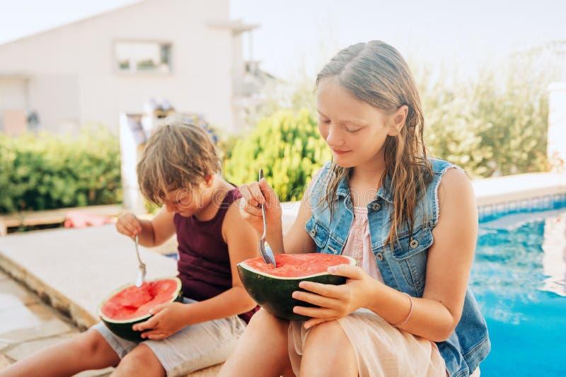 Utomhus- sommarstående av två roliga ungar som äter vattenmelon arkivfoto