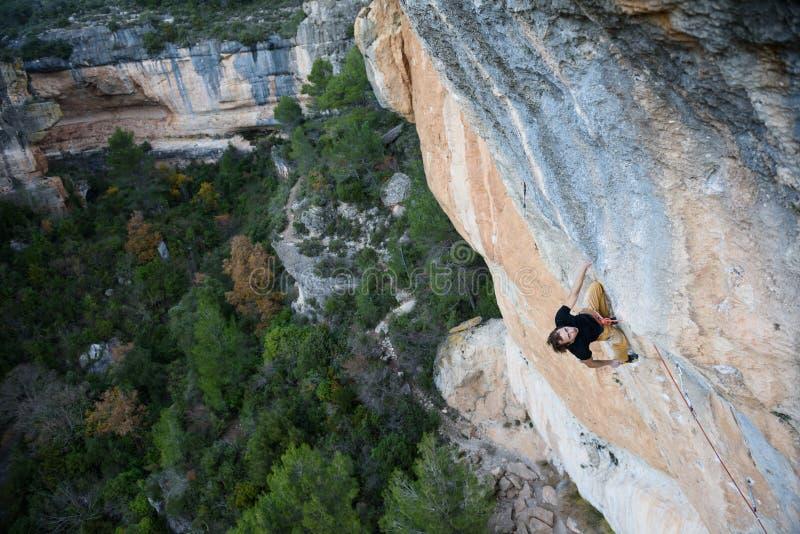 utomhus- sport Vagga klättraren som har en vila på en klippa Extrem sportklättring arkivbilder