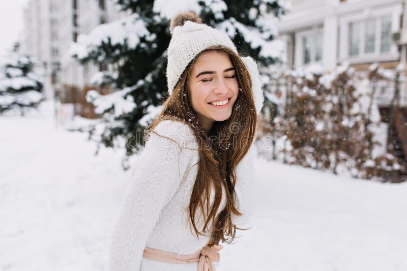 Utomhus- stående av att fascinera brunettdamen som poserar med romantiskt leende på snöig bakgrund Foto av nätt skratta royaltyfria foton