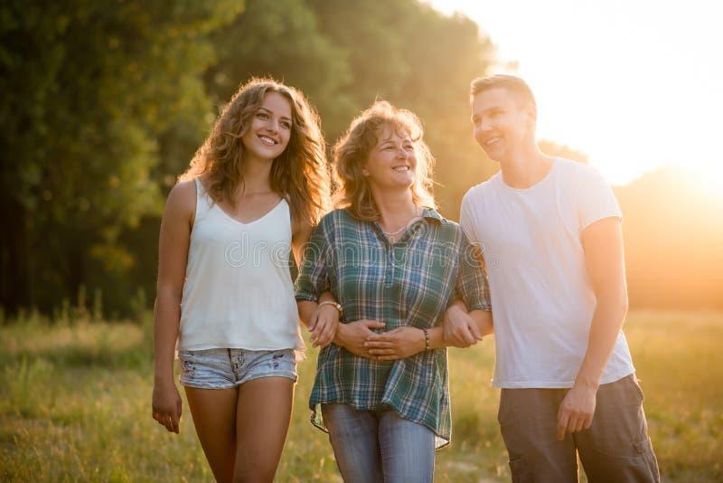 Utomhus- stående av att le den lyckliga höga modern med hennes barn fotografering för bildbyråer