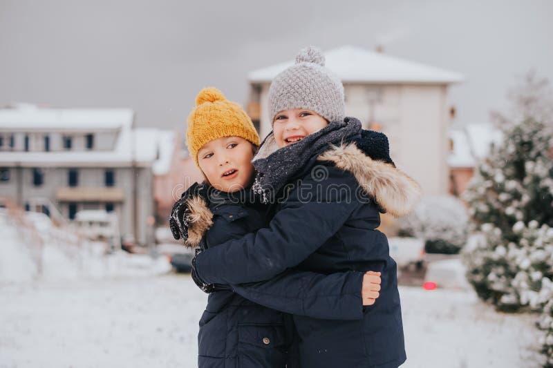 Utomhus- stående av barn 6 åriga pojkar som bär det varma omslaget arkivfoton
