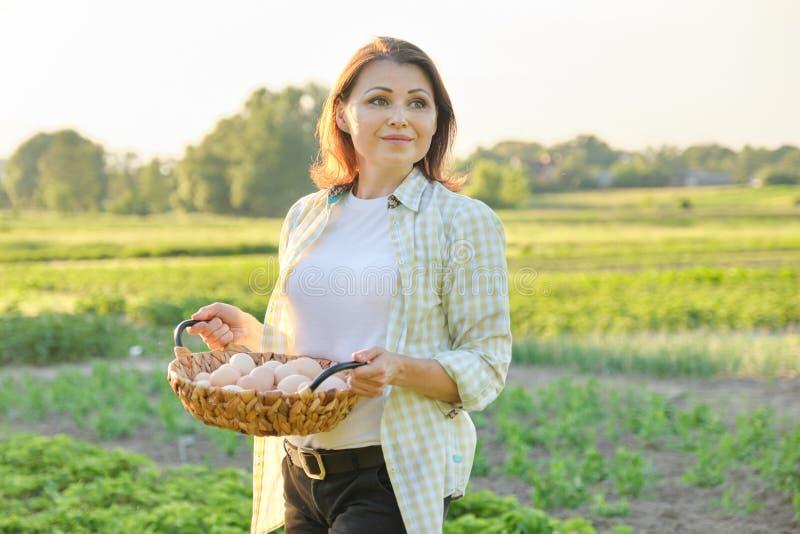 Utomhus- stående av bondekvinnan med korgen av nya fega ägg, lantgård royaltyfri foto