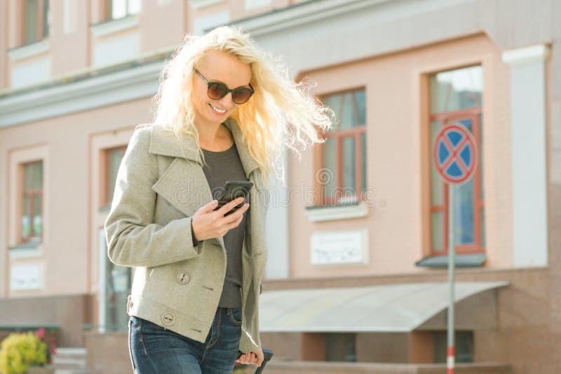Utomhus- stående av den blonda kvinnan med lockigt hår med smartphonen i hennes händer, stadsgatabakgrund arkivbild