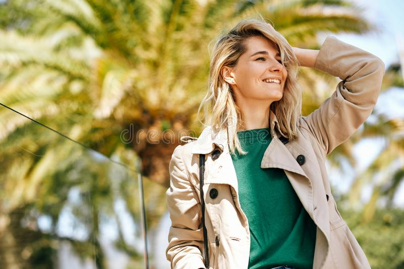 Utomhus- stående av den franka härliga blonda kvinnan som ler och tycker om det varma vädret på gatan Resor royaltyfria bilder