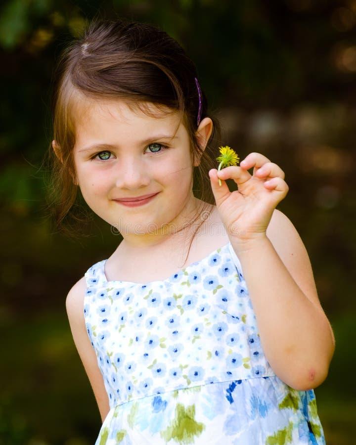 Utomhus- stående av den gulliga ung flickaholdingblomman royaltyfria bilder