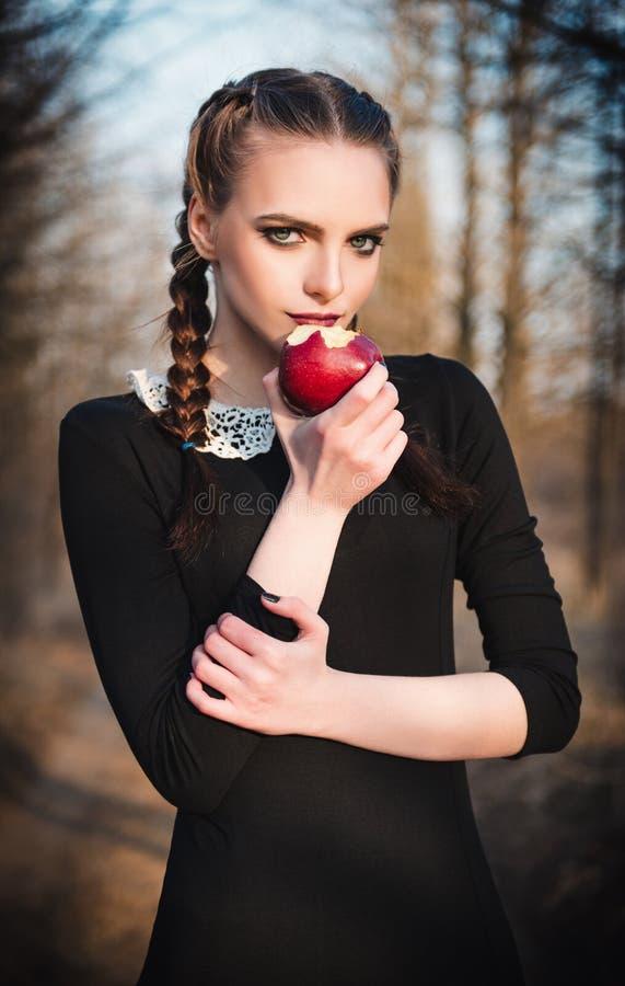 Utomhus- stående av den gulliga unga flickan i gammalmodig klänning som äter det röda äpplet arkivfoton