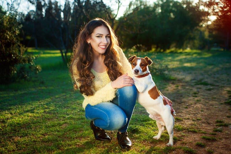 Utomhus- stående av den härliga flickan och den Jack Russell för älsklings- hund terriern arkivfoto