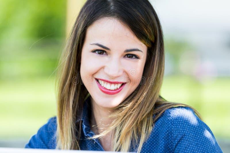 Utomhus- stående av den härliga le unga kvinnan royaltyfri fotografi