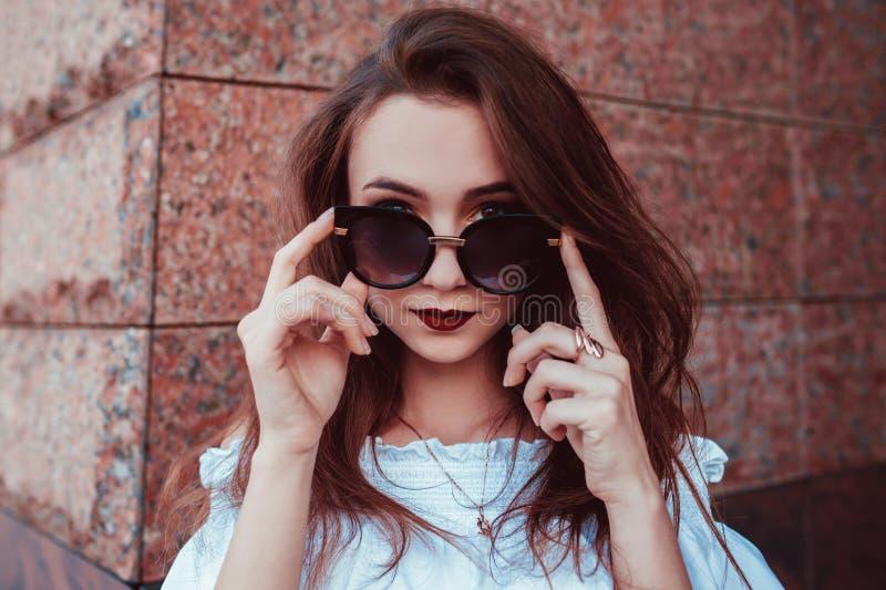 Utomhus- stående av den härliga stilfulla kvinnan i exponeringsglas på gatan Kläder och tillbehör för sommar för modemodell bäran royaltyfri foto
