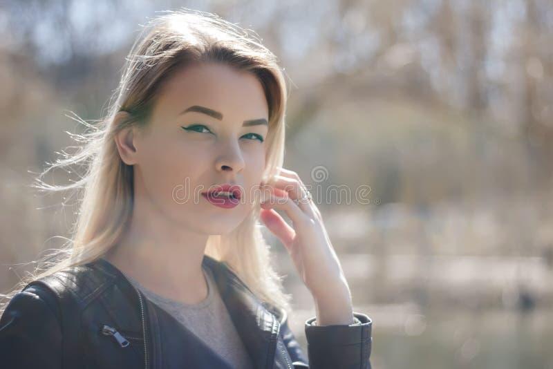 Utomhus stående av den härliga unga brunettflickan Le för kvinna som är lyckligt på solig sommar eller vårdag utanför på stadsbak fotografering för bildbyråer