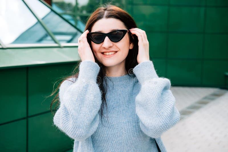 Utomhus stående av den härliga unga brunettflickan som ler, slut upp Tonåringhipsterflicka med solglasögon som bär den moderiktig royaltyfri fotografi