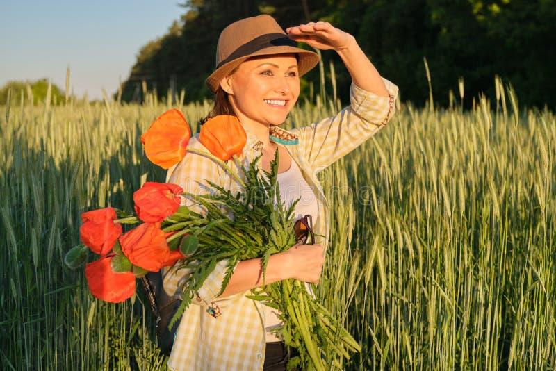 Utomhus- stående av den lyckliga mogna kvinnan med buketter av röda vallmoblommor arkivfoton
