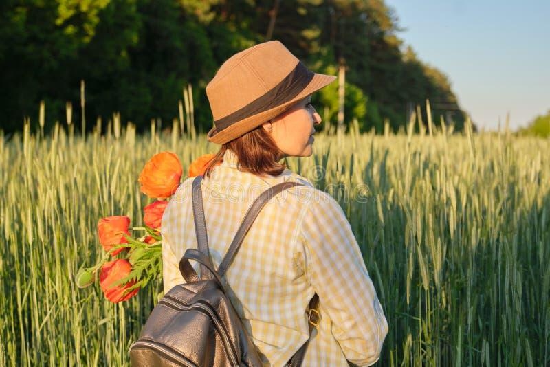 Utomhus- stående av den lyckliga mogna kvinnan med buketter av röda vallmoblommor arkivfoto