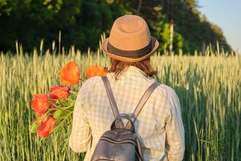 Utomhus- stående av den lyckliga mogna kvinnan med buketter av röda vallmoblommor fotografering för bildbyråer