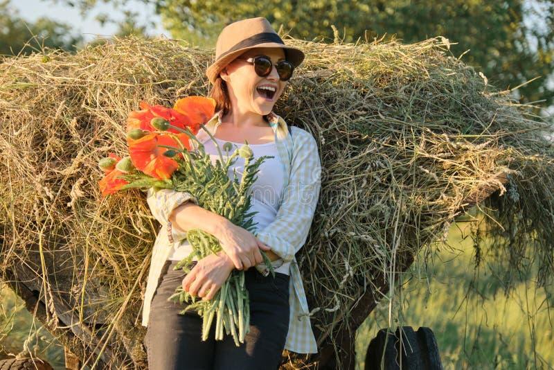 Utomhus- stående av den lyckliga mogna kvinnan med en bukett av röda blommor för vallmo arkivbild