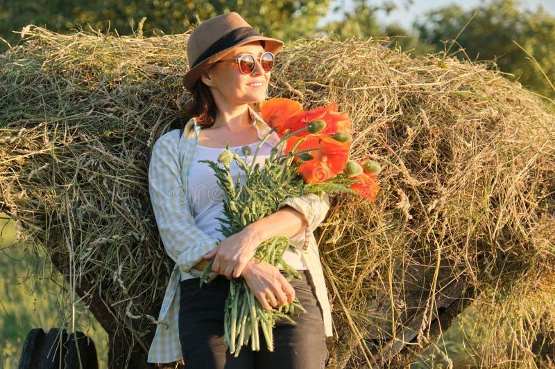 Utomhus- stående av den lyckliga mogna kvinnan med en bukett av röda blommor för vallmo royaltyfri fotografi