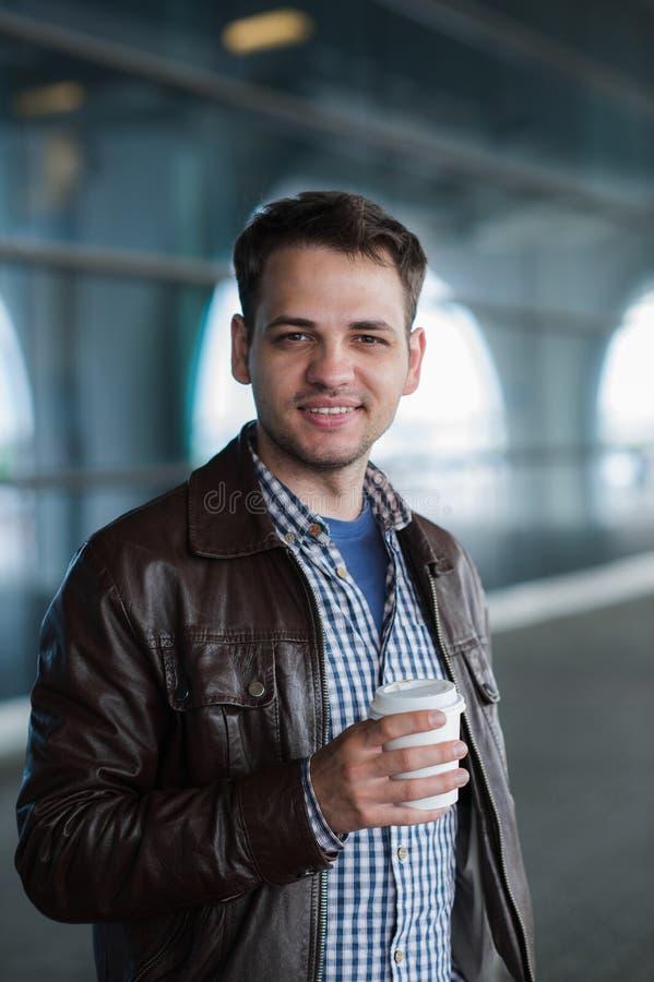 Utomhus- stående av den moderna unga mannen med kaffe som går kopp som ler royaltyfri foto
