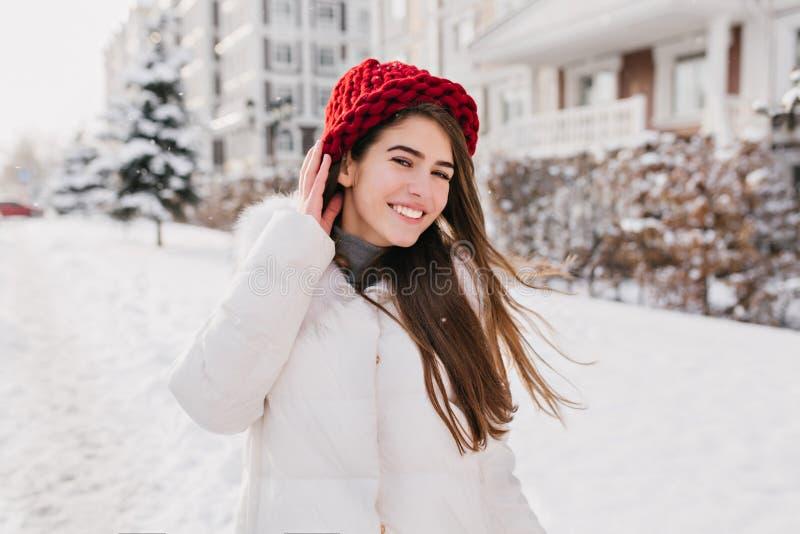 Utomhus- stående av den nöjda långhåriga damen i röd stucken hatt som går ner gatan i snöig helg Foto av arkivbilder