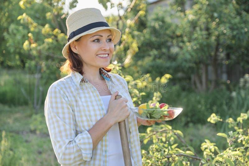 Utomhus- stående av den positiva mogna kvinnan i sugrörhatt Le kvinnlign med plattan av jordgubbemintkaramellcitronen, bakgrundsg fotografering för bildbyråer