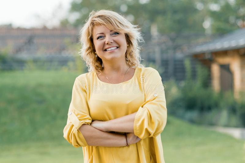 Utomhus- stående av den positiva säkra mogna kvinnan Le den kvinnliga blondinen i en gul klänning med armar som korsas nära huset royaltyfri fotografi