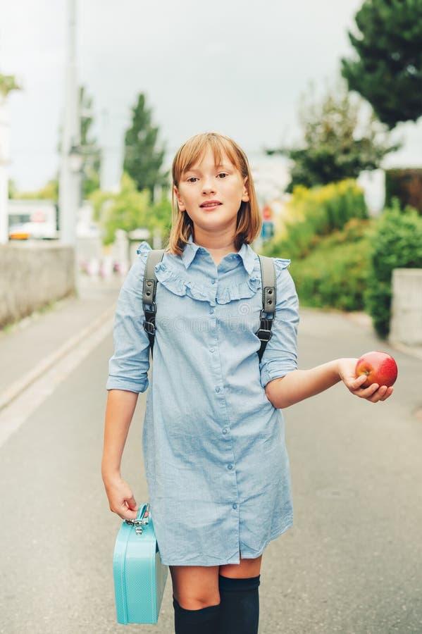 Utomhus- stående av den roliga lilla skolflickan royaltyfria foton