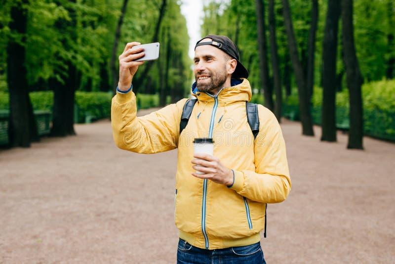 Utomhus- stående av den stilfulla mannen med skäggstubbskägget som bär den gula anorak- och innehavryggsäcken och takeaway wi för royaltyfri fotografi