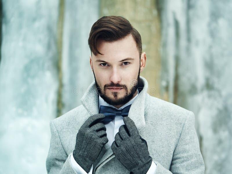 Utomhus- stående av den stiliga mannen i grå färglag arkivfoto