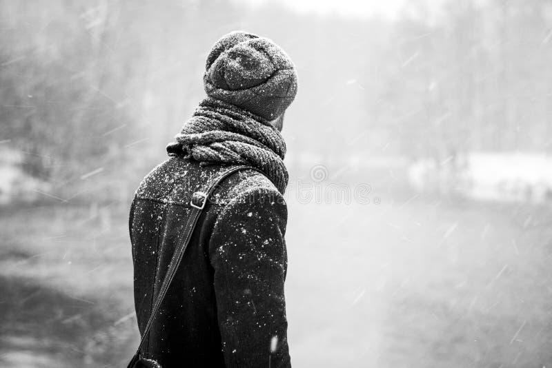 Utomhus- stående av den stiliga unga mannen i snöig vinterskogsnöfall Grabb som ser bort på den djupfrysta floden svart white royaltyfria bilder