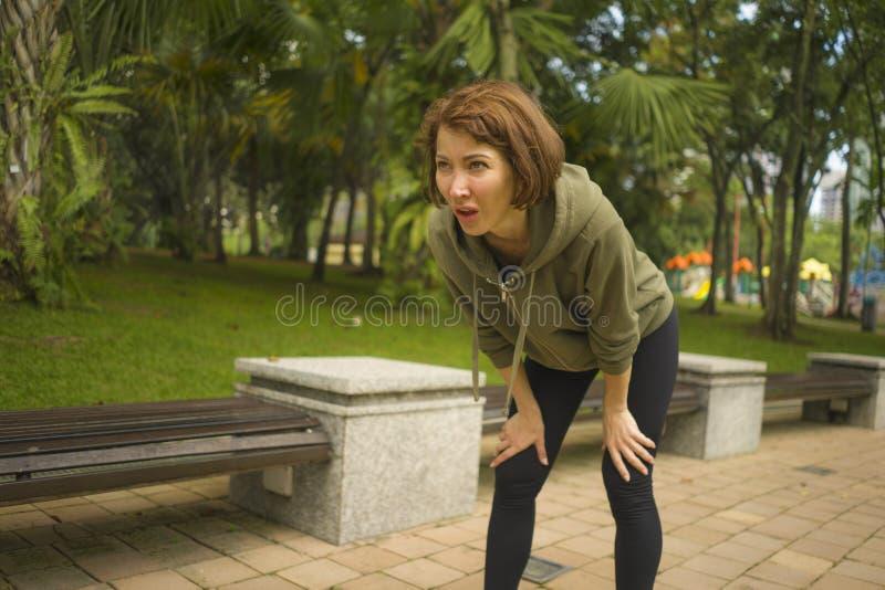 Utomhus stående av den unga attraktiva trötta och andfådda joggerkvinnan, i att andas som evakueras, når att ha kört genomkörare  arkivfoto