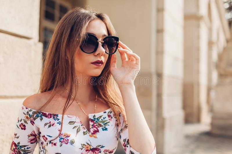Utomhus- stående av den unga härliga trendiga kvinnan som bär stilfull solglasögon Stadsmode makeup fotografering för bildbyråer
