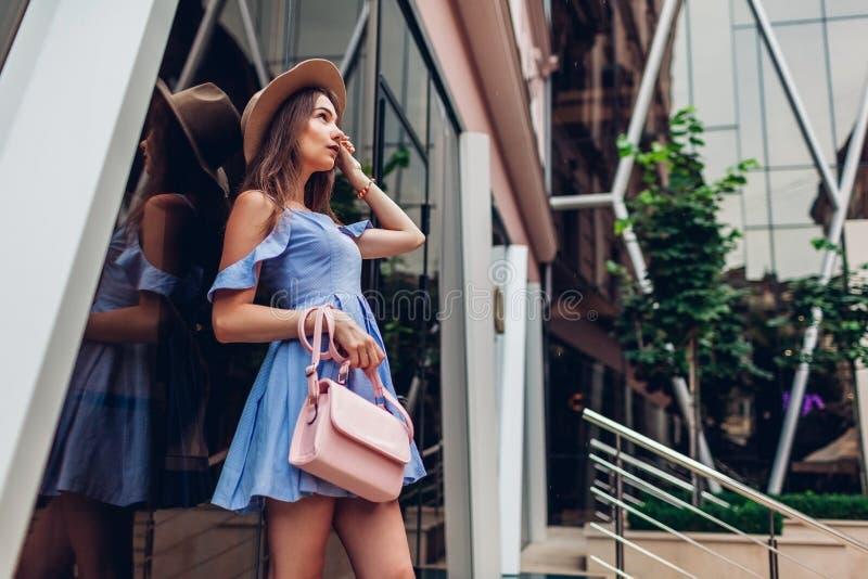 Utomhus- stående av den unga härliga trendiga kvinnan som bär stilfull tillbehör Flicka som döljer från regn i stad royaltyfri foto