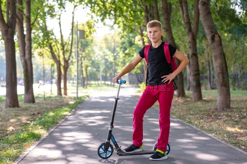 Utomhus- stående av den unga lyckliga preteen pojken som rider en sparkcykel på naturlig bakgrund arkivfoto
