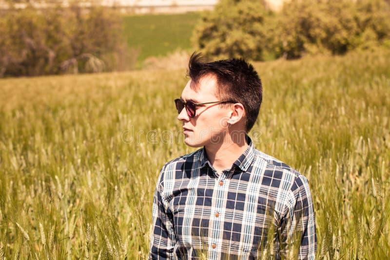Utomhus stående av den unga mannen i solglasögon på bygden royaltyfri fotografi