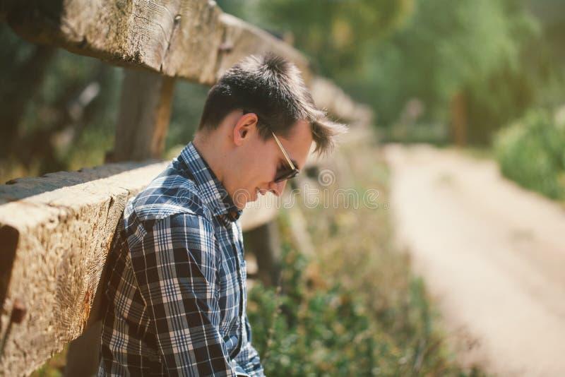 Utomhus stående av den unga mannen i solglasögon på bygden royaltyfria foton