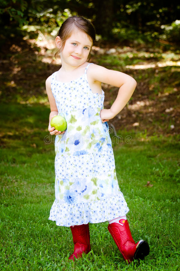 Utomhus- stående av det gulliga ung flickaholdingäpplet royaltyfri fotografi