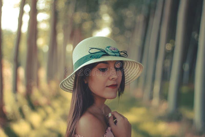 Utomhus- stående av en bärande sommarhatt för ung kvinna fotografering för bildbyråer