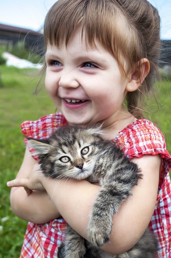 Utomhus- stående av en gullig liten flicka med den lilla kattungen, flicka som spelar med katten på naturlig bakgrund royaltyfri fotografi