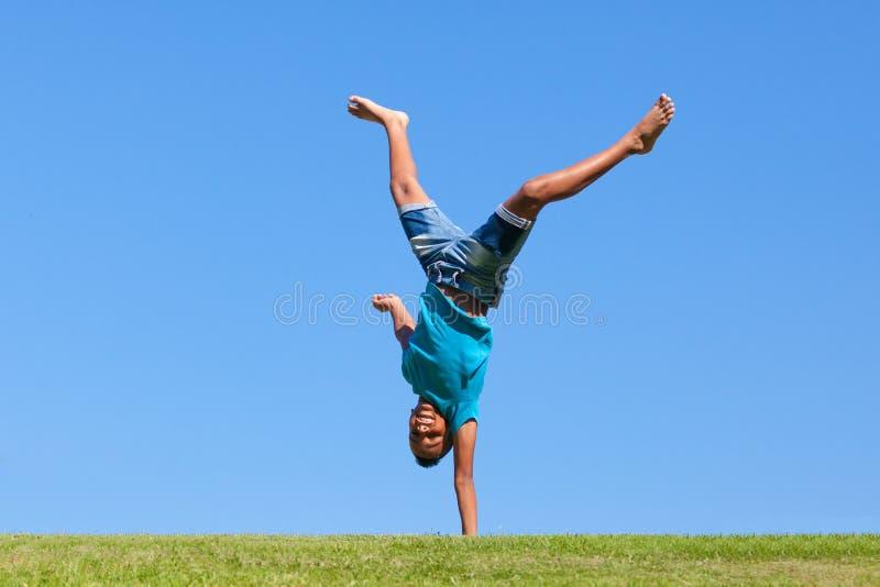 Utomhus- stående av en gullig tonårs- svart pojkebanhoppning arkivfoton