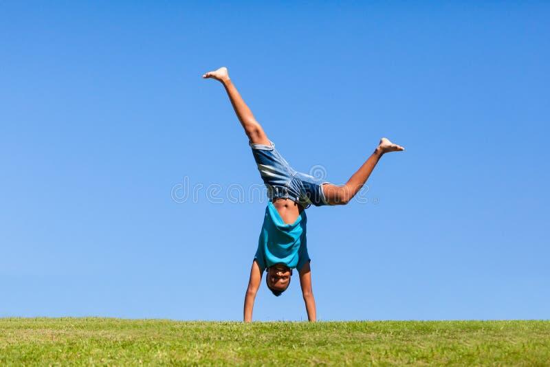 Utomhus- stående av en gullig tonårs- svart pojkebanhoppning royaltyfri foto