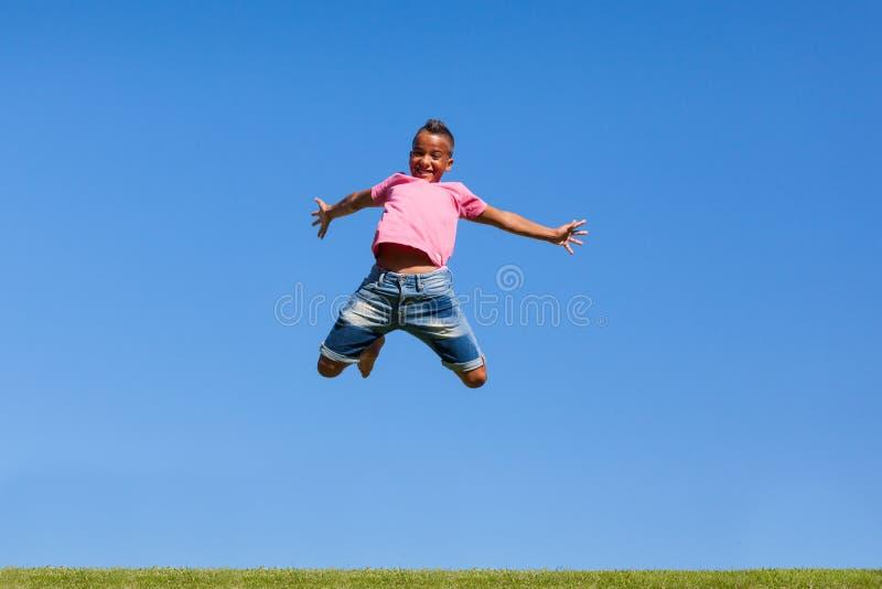 Utomhus- stående av en gullig tonårs- svart pojkebanhoppning arkivfoto