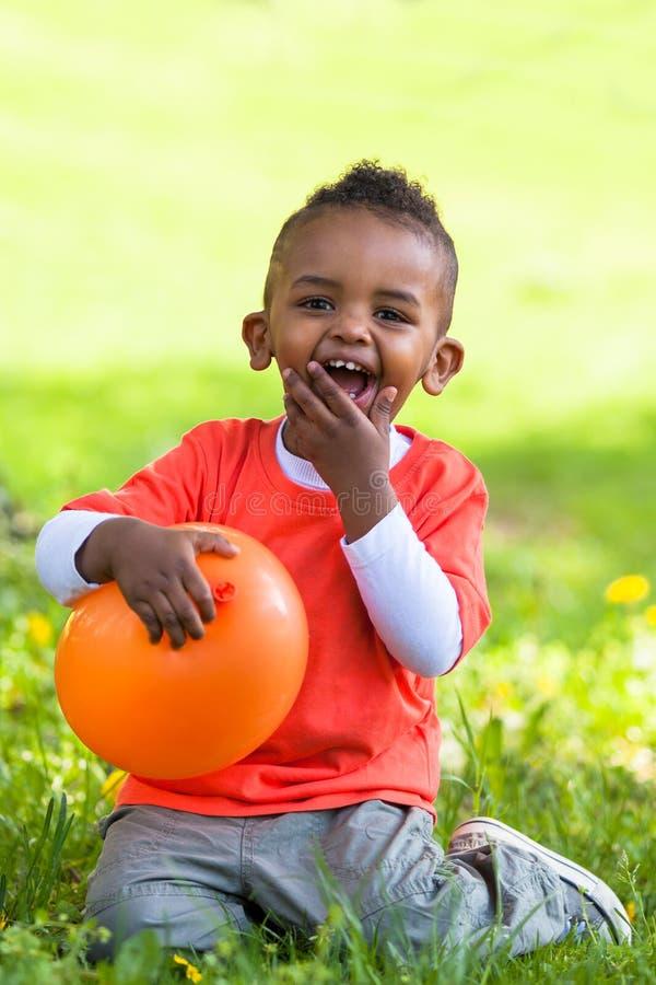 Utomhus- stående av en gullig ung liten svart pojke som spelar med royaltyfri bild