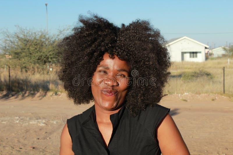 Utomhus- stående av en härlig afrikansk kvinna med afro hår royaltyfria bilder