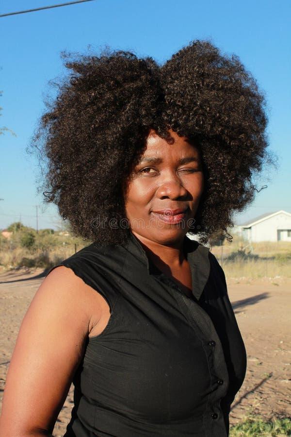 Utomhus- stående av en härlig afrikansk kvinna som blinkar ett öga arkivfoto
